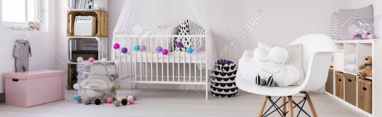 Chambre enfant moderne avec une simple lit bébé, chaise blanche et,  éléments décoratifs colorés