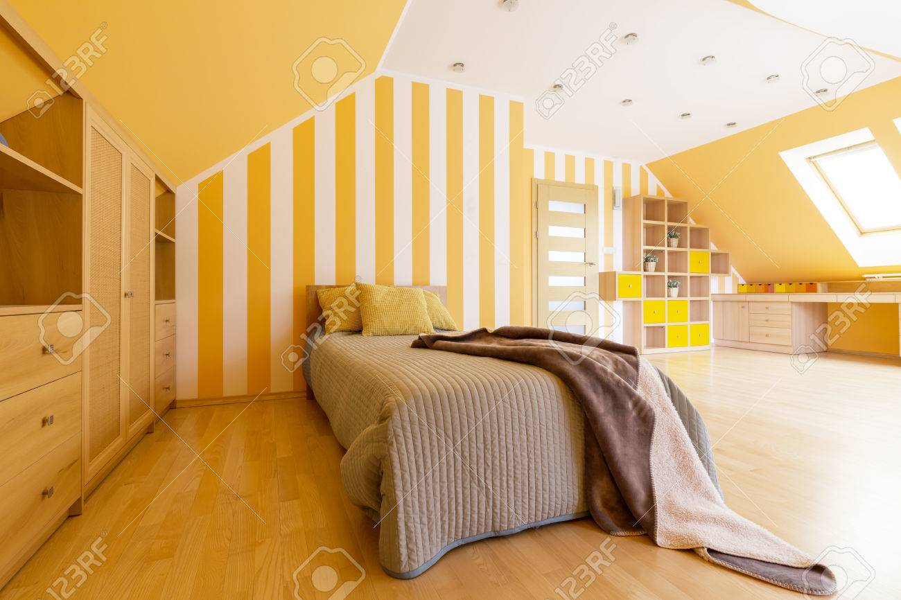 Shot of a spacious modern bedroom with orange walls