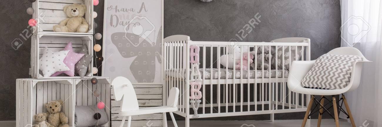 La chambre de petite fille moderne avec des meubles blancs, porte-boîte en  bois et décorations pastel subtiles
