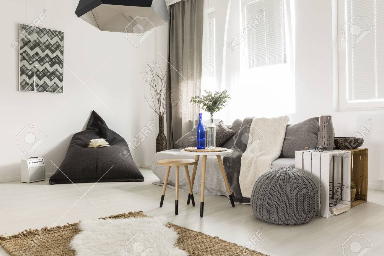 Light livng room with bean bag, comfortable sofa, DIY table, window and stylish decorative details Standard-Bild - 63816213
