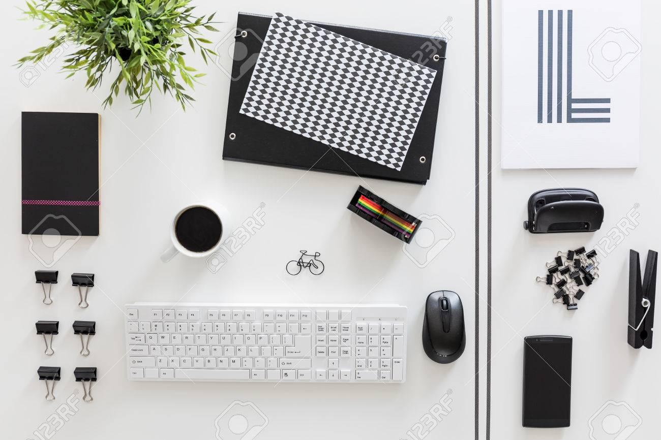 Bureau blanc avec papiers blanc et noir ordonnés de manière