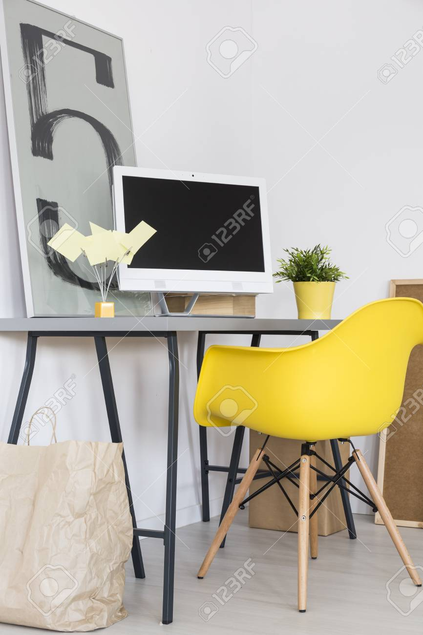 Minimalist Home Office With Simple Desk, Yellow Chair, Computer And  Decorative Painting On The