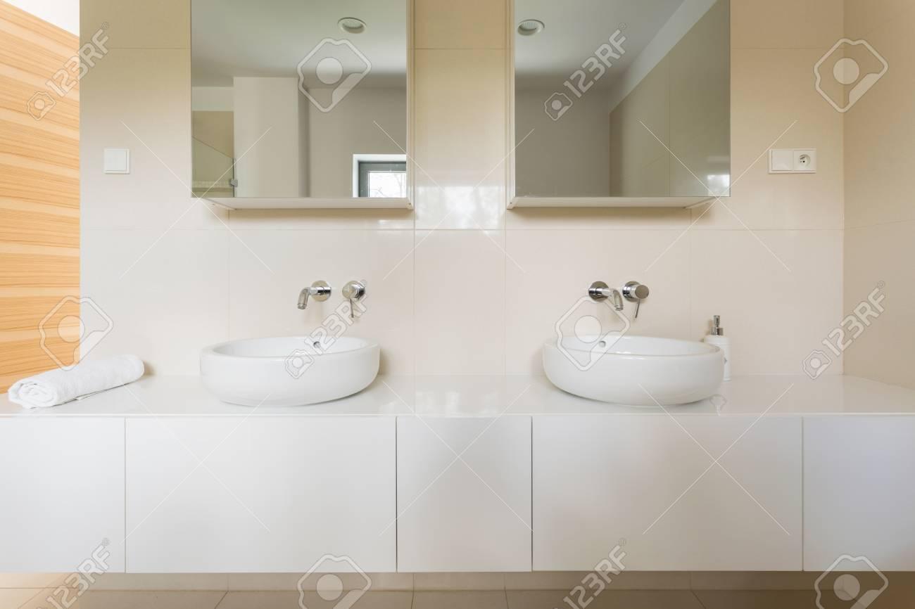 Helles Badezimmer Mit Weißen Fliesen, Zwei Becken Und Spiegel Standard Bild    63816009
