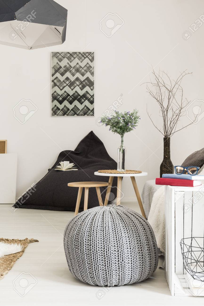 Modern living room in white with stylish pendant lamp, pouf,..