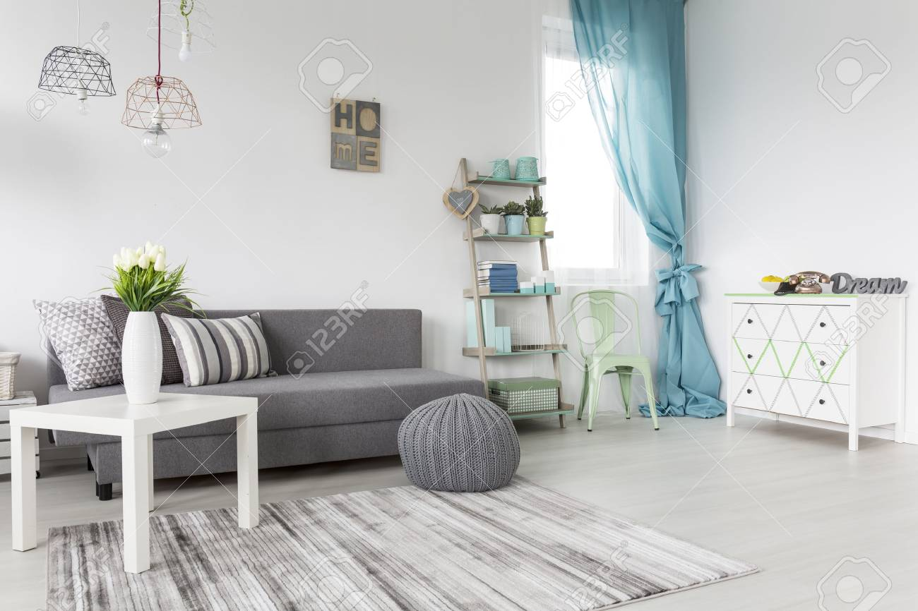 Grey living room with a mint curtains and white walls