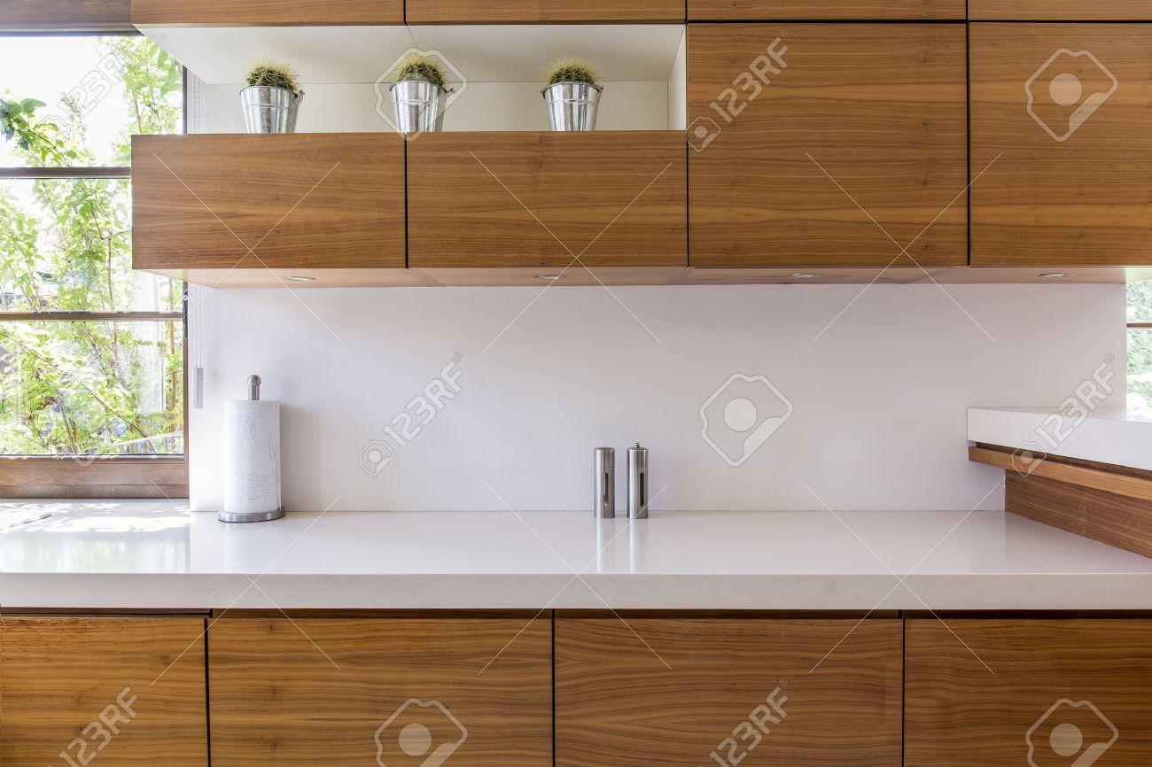 muebles de cocina de madera y encimera de blanco en un interior moderno foto de archivo