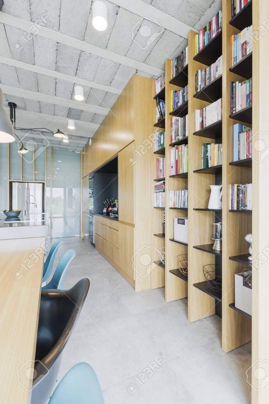 Plafond en béton et bibliothèque en bois dans la maison contemporaine