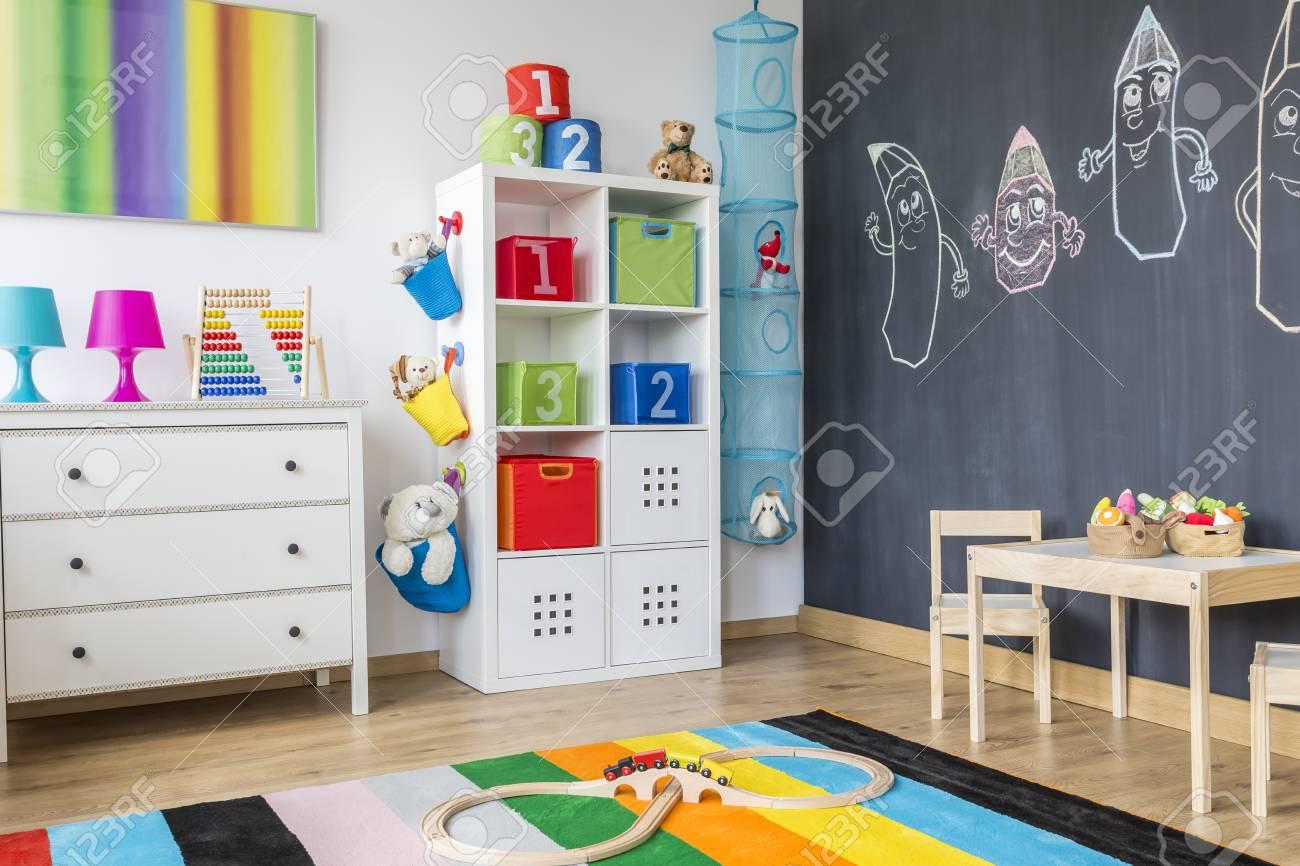 Une Partie De Chambre Colorée Enfant Avec Armoire, Commode Et Table ...