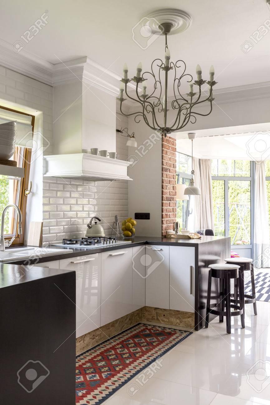 Offene Küche Mit Weißen Einbaumöbeln, Gemustertem Teppich, Stilvollem  Kronleuchter Und Terrasseneintrag Standard Bild