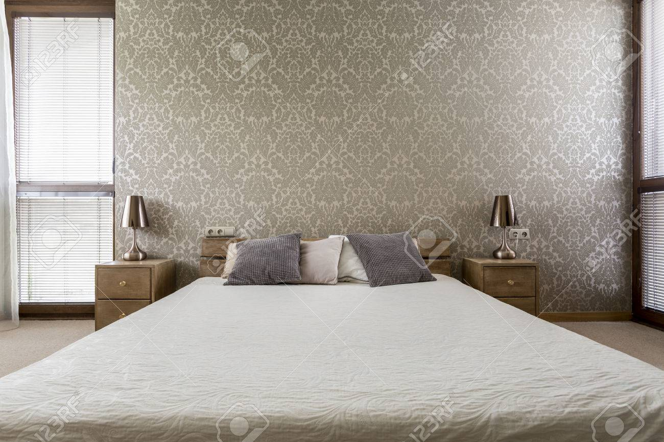 Light Bedroom With Decorative Wallpaper And Large Double Bed Stock Photo    65140089