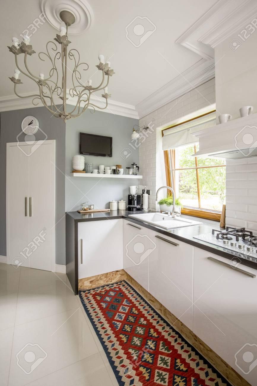 Gut Offene Küche Mit Weißen Einbaumöbeln, Gemusterten Teppich, Fenster Und  Stilvolle Kronleuchter Standard Bild