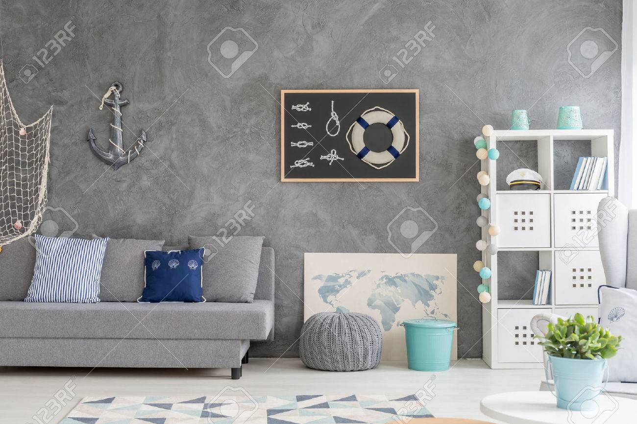 Grey Home Interior With Nautical Wall Decor, Sofa, Carpet And White Storage  Unit Stock