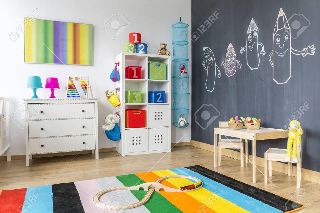 Vue de la chambre des enfants avec tapis coloré et le mur tableau noir