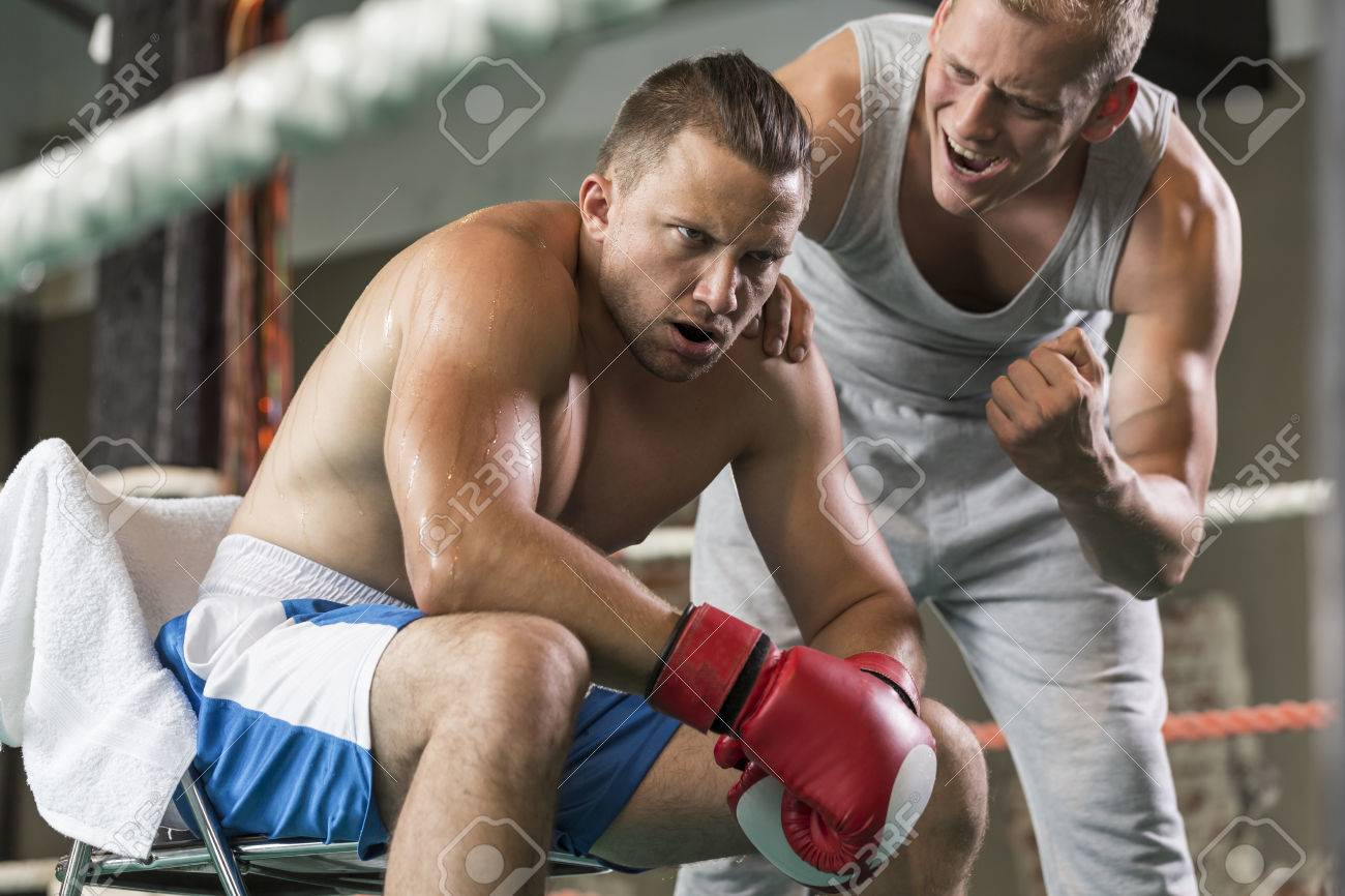 athletic coach motivating tired boxer during fight on a ring stock photo 65811358