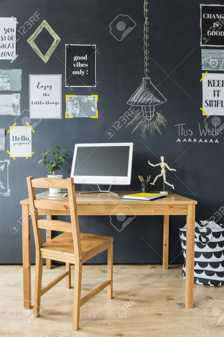 Wooden computer desk and chair by a chalkboard wall with optimistic..