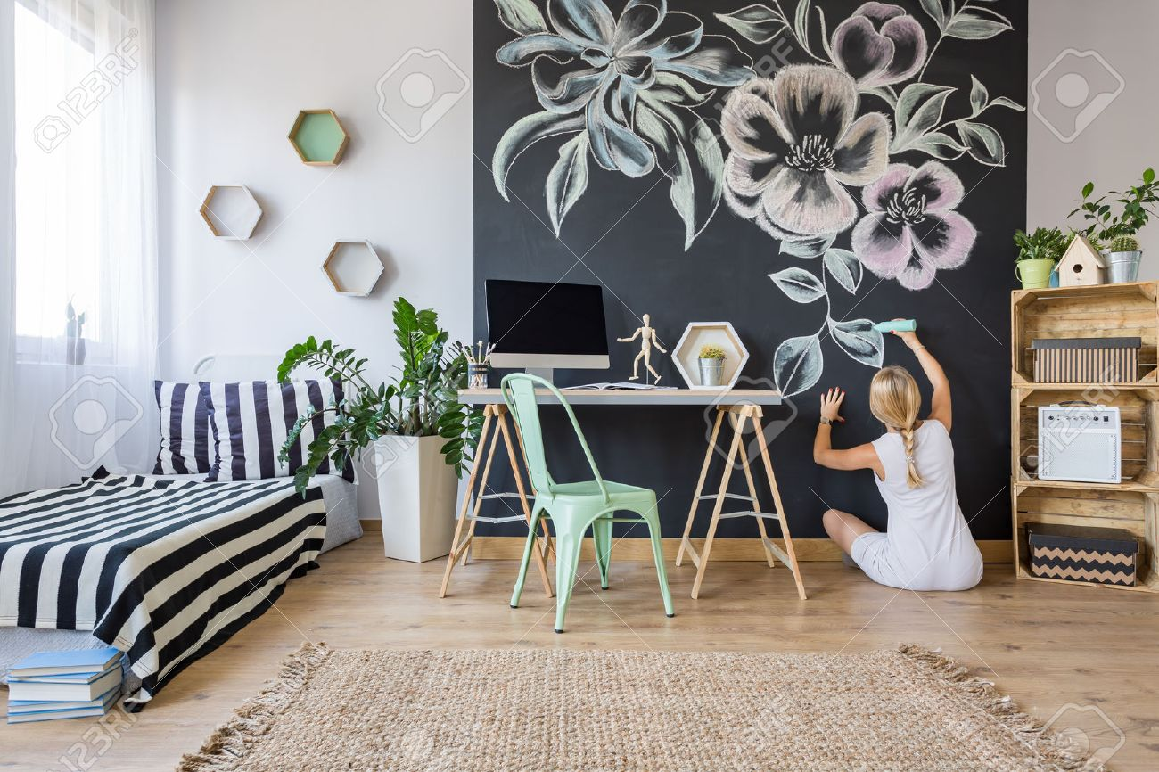 Woman drawing flowers on chalkboard wall in multifunctional home interior Stock Photo - 66123756