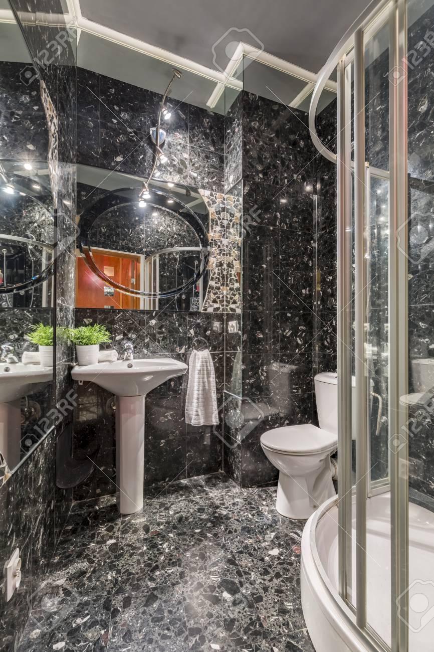 Intérieur de salle de bain ethnique en marbre gris colous, avec lavabo,  miroir ci-dessus, rétro-éclairage, toilettes et douche
