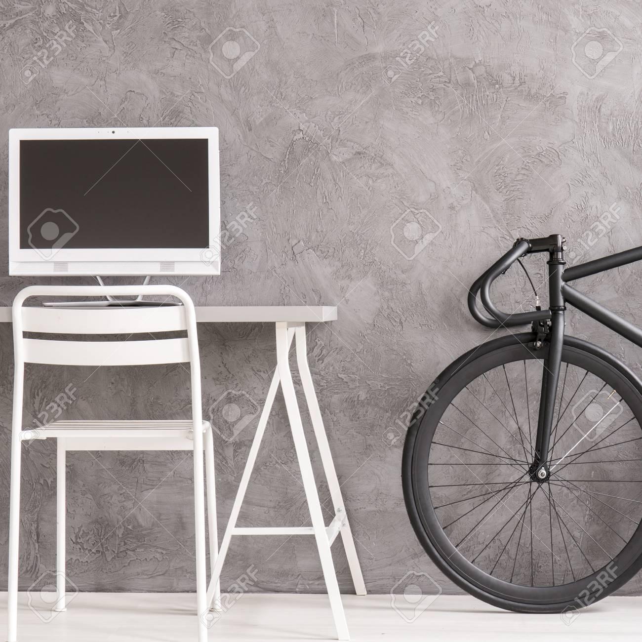Chambre de l\'adolescent minimaliste moderne avec mur gris, bureau blanc et  chaise, vélo noir