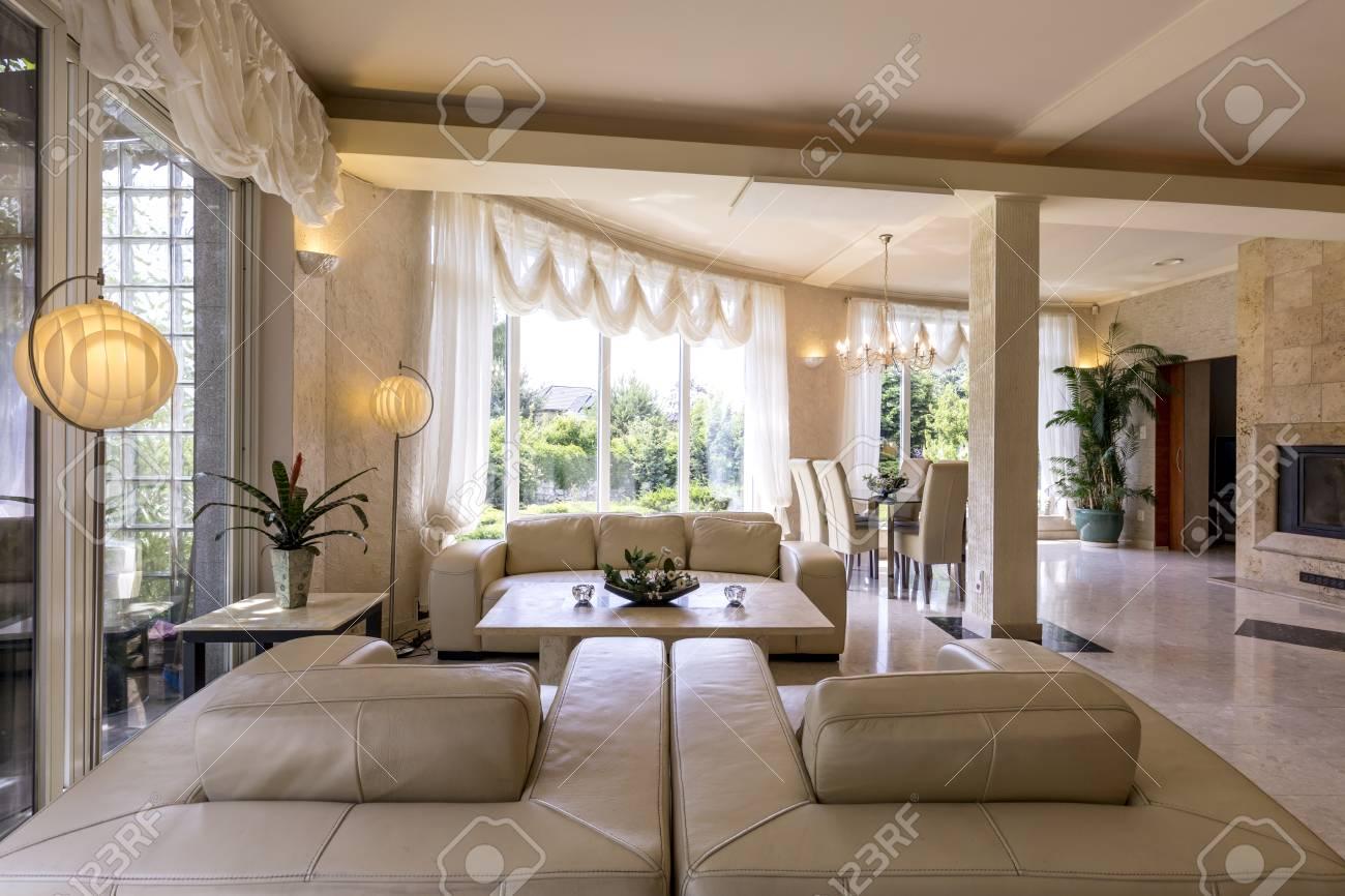 Luminoso, interior de sala de estar de mármol diseñado, rodeado de  ventanas, sofá de cuero y sillones, comedor con sillas, lámpara de araña,  lámparas ...