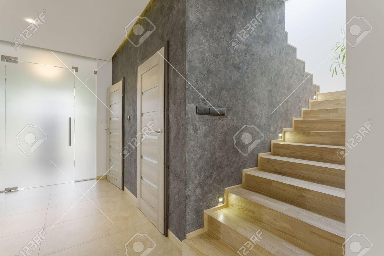 antesala moderna con escalera de madera puerta de cristal de la leche y la pared