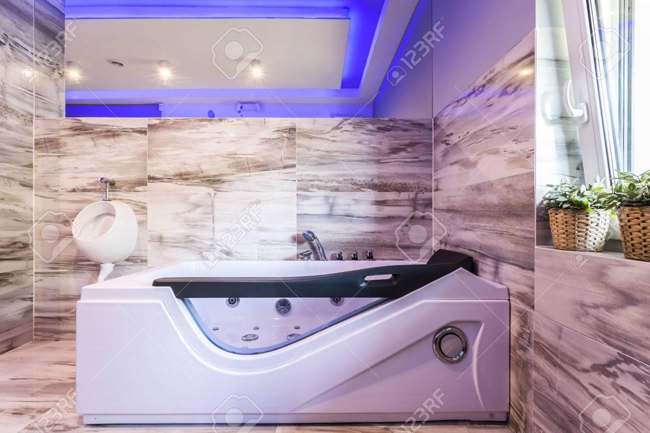 Baignoire moderne avec jacuzzi confortable et urinoir dans une salle de  bains carrelée