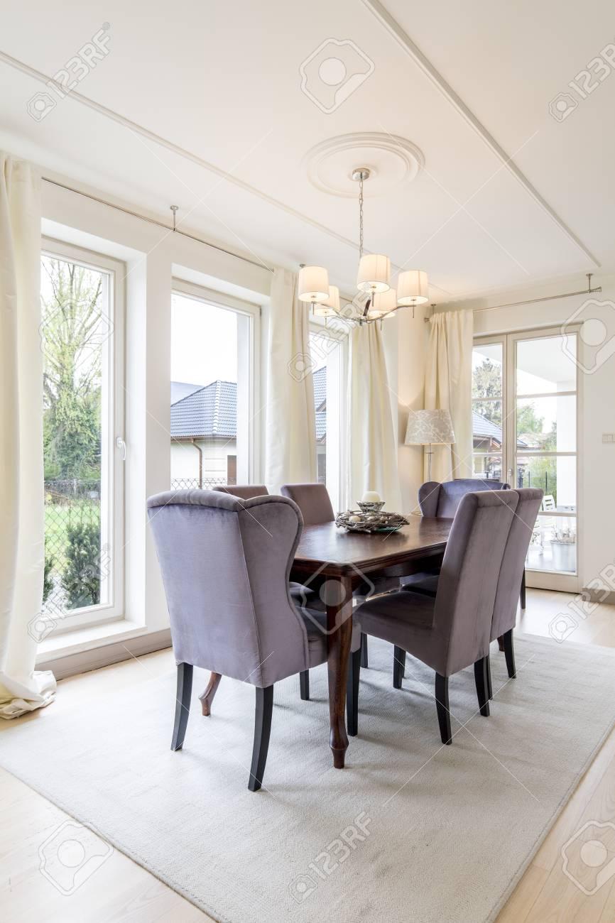 Chambre chic et éclairée avec une table et des chaises en bois massif