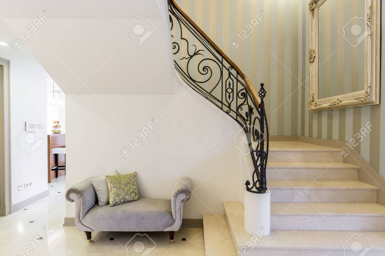 elegant staircase with decorative railing big framed mirror and patterned couch stock photo 67267379