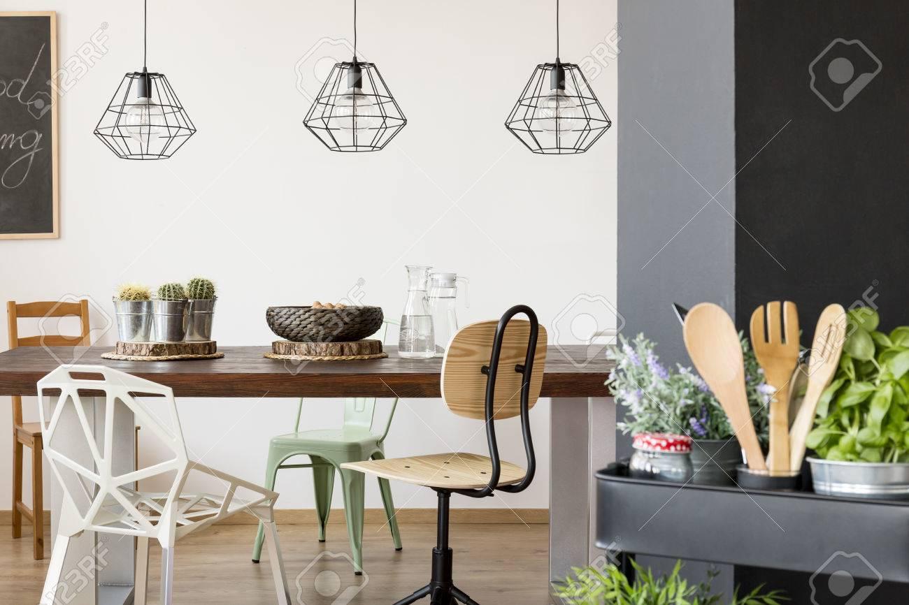 Habitación con mesa común, sillas, lámparas de techo, cocina cesta