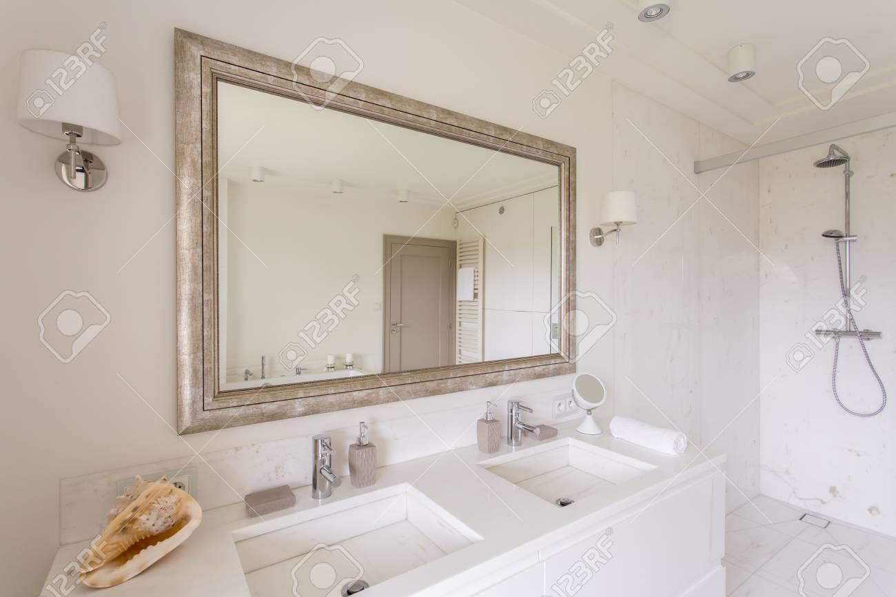Cuarto de baño minimalista con un gran espejo en un marco decorativo y dos  lavabos de mármol