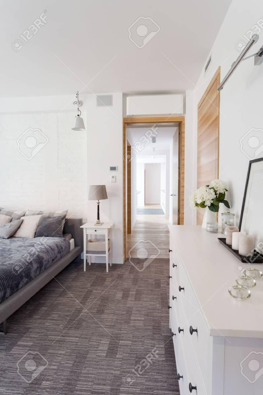 Camera da letto matrimoniale elegante con grande letto grigio e comò bianco