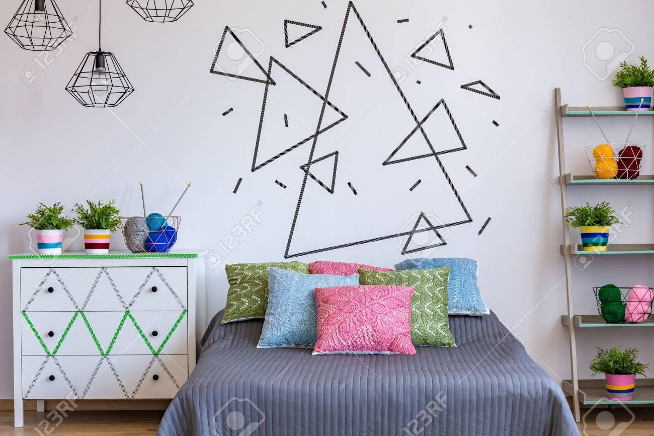 coin chambre avec lit coloré, commode et mur blanc avec le thème de
