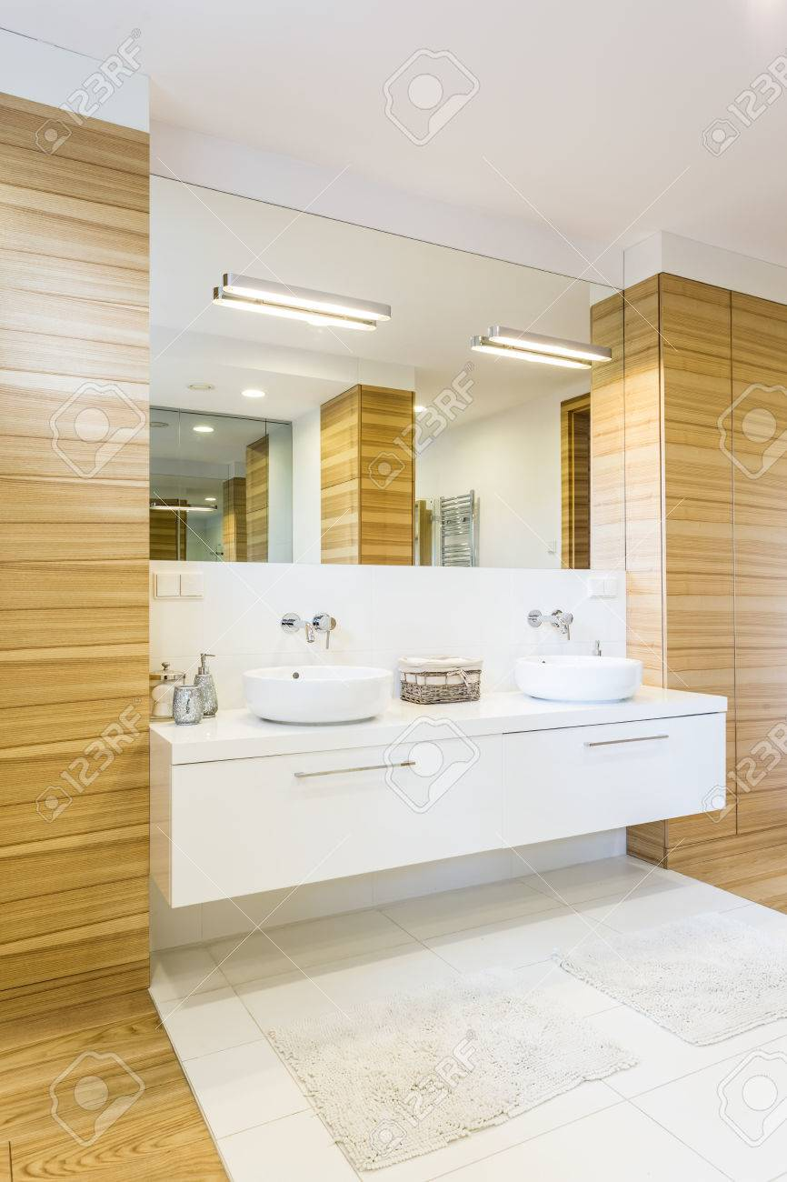 Large Spacious Bathroom Finished In Wood With Large Mirror And Two White  Sinks Stock Photo