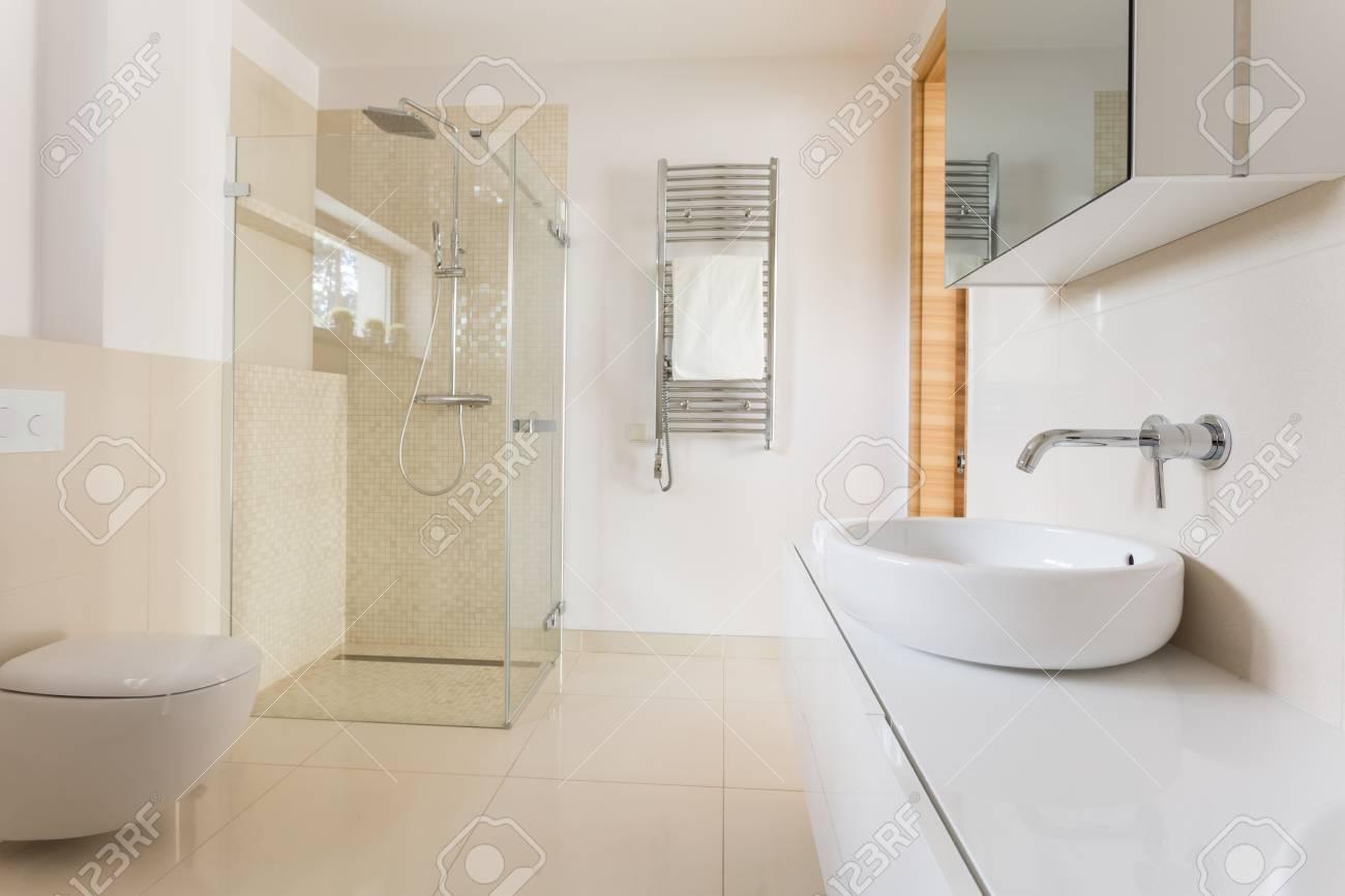Amplio cuarto de baño moderno con los azulejos brillantes con ducha de  cristal, inodoro y lavabo