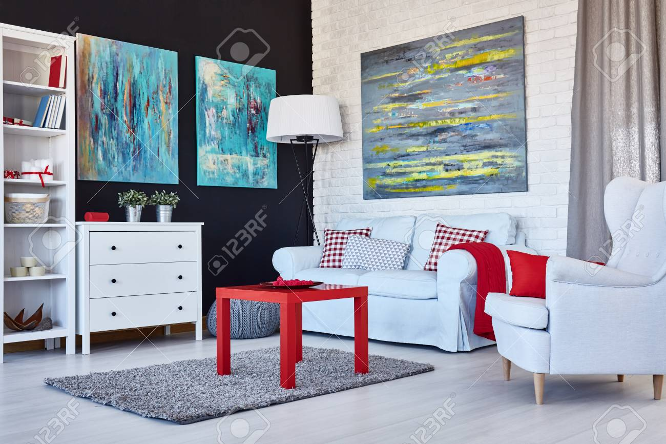 Cozy modern living room with white furniture, blue paintings..