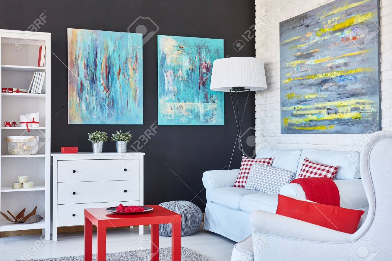 Stylish living room decorated with art and red accessories