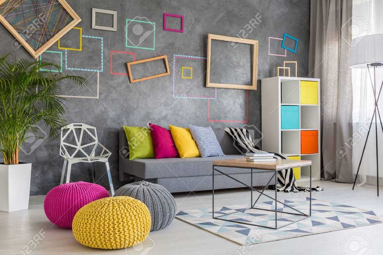 Salon moderne spacieux avec un canapé gris et coussins colorés et poufs
