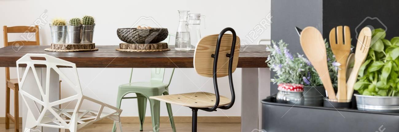 Modernes Esszimmer Mit Großem Holztisch, Verschiedenen Stühlen Und  Küchenutensilien Standard Bild   68146771