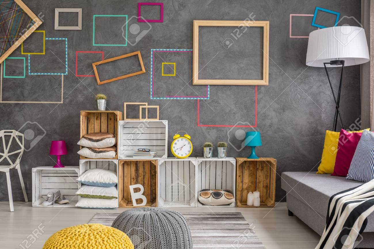 Salon moderne gris avec étagère en bois pleine de décorations colorées