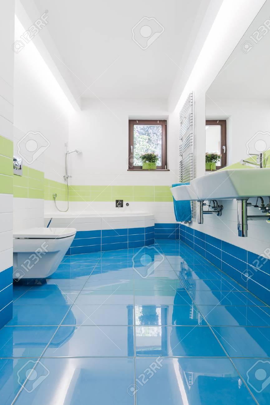 Intérieur petite salle de bains colorée avec carrelage bleu, WC, lavabo et  baignoire deux