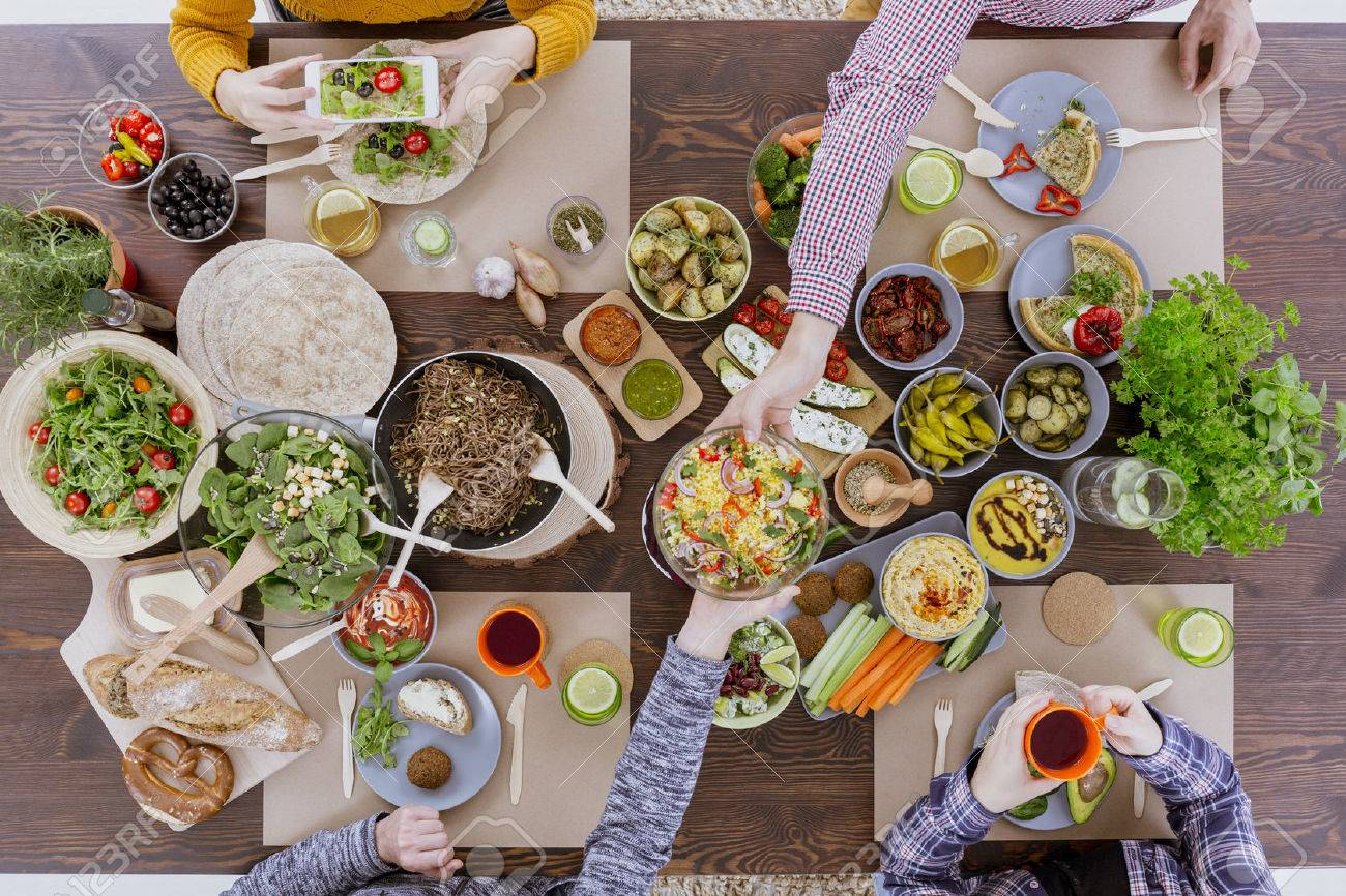 Friends having vegetarian feast, sitting at rustic table - 68548694