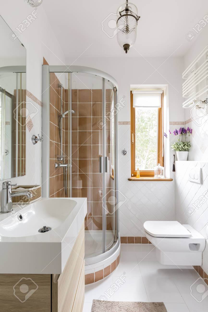small functional modern bathroom with toilet sink and glass stock
