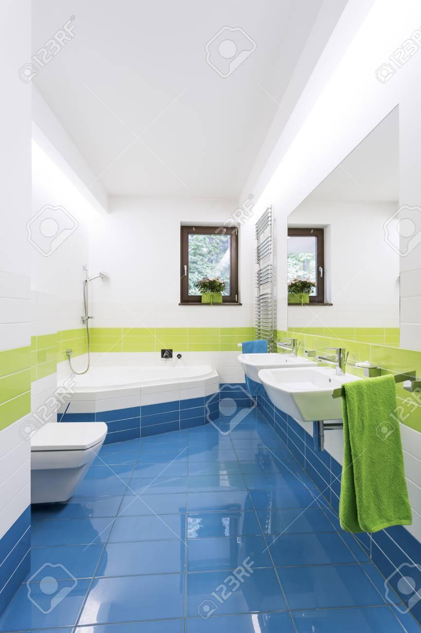 Salle de bain moderne colorée avec baignoire, lavabos et toilettes avec  carrelage bleu et vert