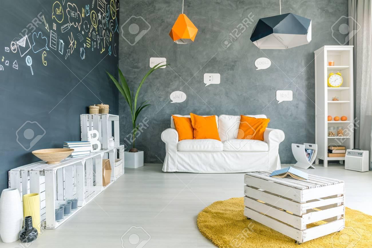 Chambre avec mur tableau noir, un canapé et des meubles de caisse blanche