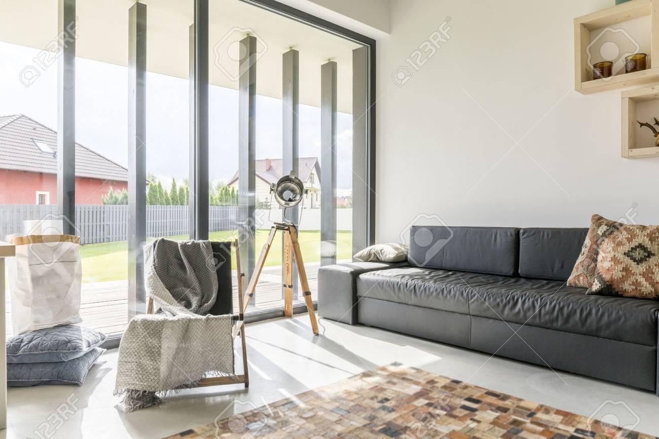 Salon avec mur de la fenêtre, un canapé noir et tapis