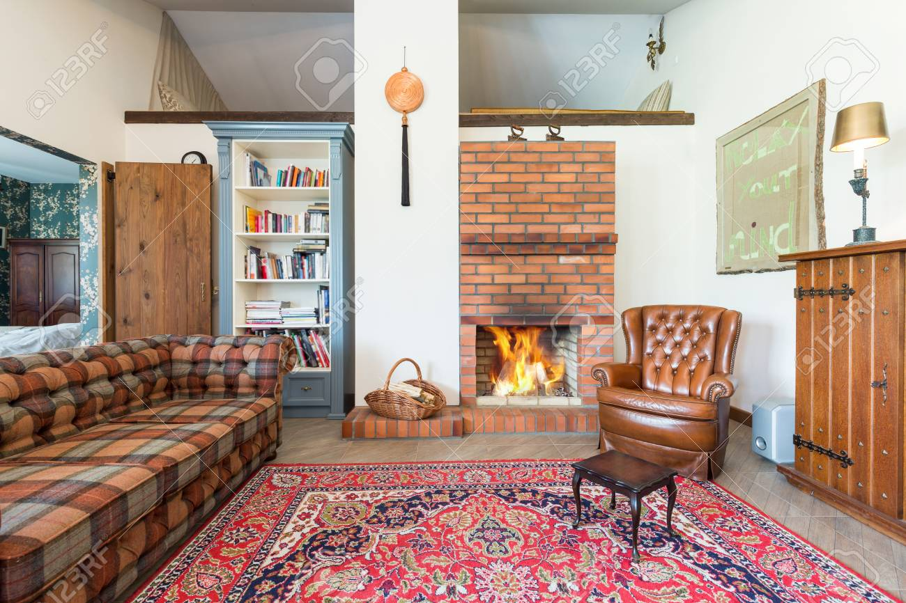 . Rustic cozy living room with bricked fireplace  couch  armchair