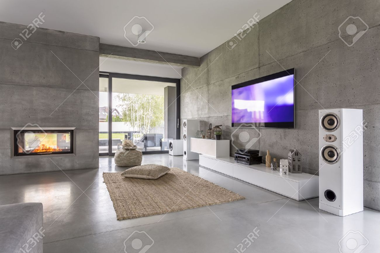 Tv living room with window, fireplace and concrete wall effect - 68553695