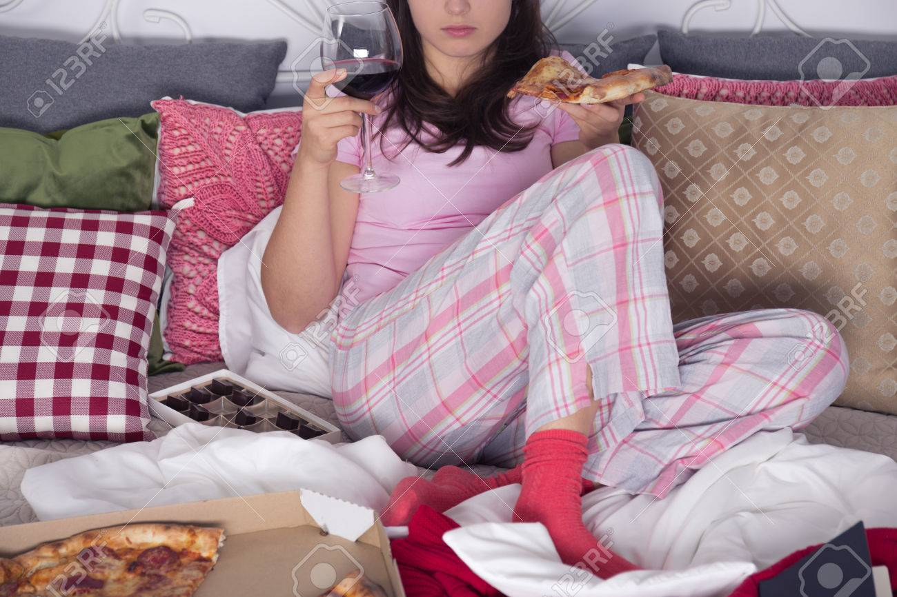 Woman sitting on couch, eating pizza and drinking wine Stock Photo - 68553728
