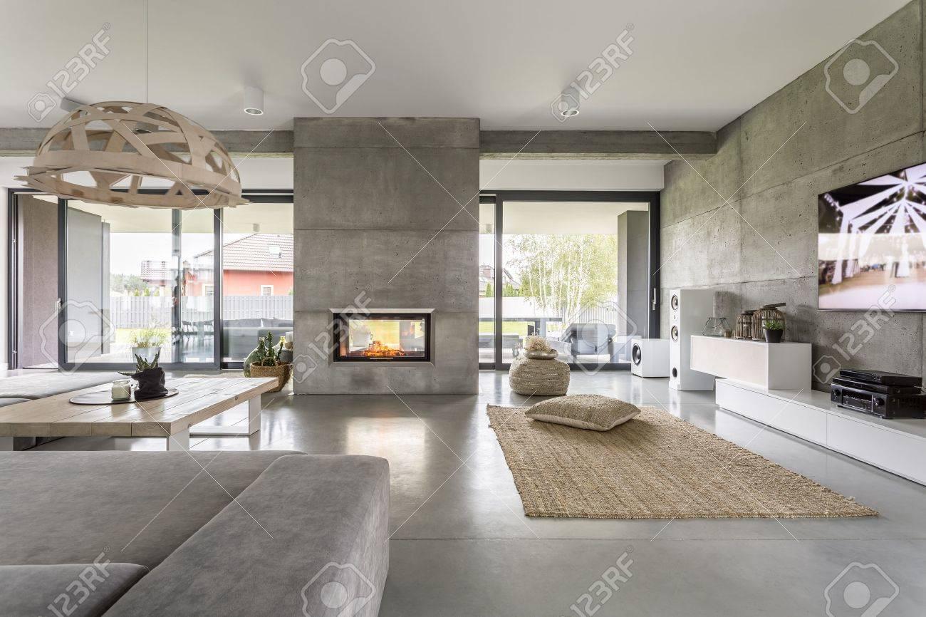 Geräumige Villa Interieur Mit Zement Wandeffekt, Kamin Und TV Standard Bild    68553748