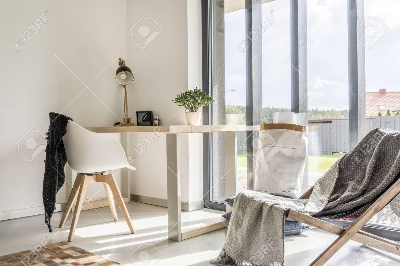 salle blanche avec transat, bureau en bois, chaise et mur de la fenêtre Banque d'images - 68553766