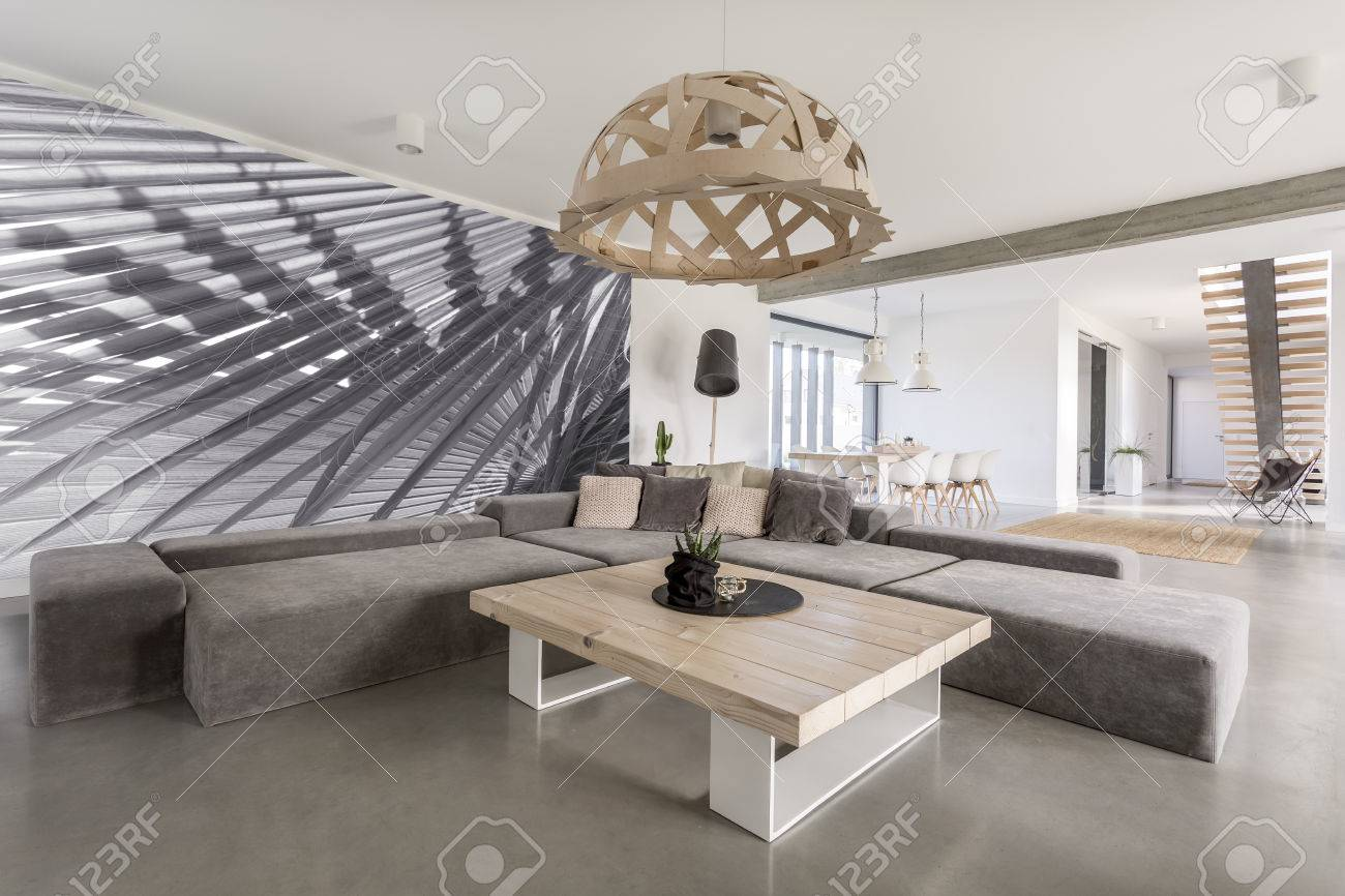 Room with extra large sofa, wooden table and photo wallpaper Stock Photo - 68553787